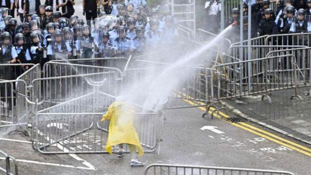 Polisi menggunakan meriam air untuk menghalau seorang demonstran dekat gedung pemerintah, Rabu (12/06).